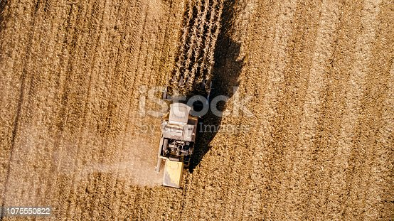 1072634078 istock photo Aerial view of combine harvester on corn field 1075550822