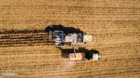 1072634078 istock photo Aerial view of combine harvester unloading corn in tractor trailer 1075550974