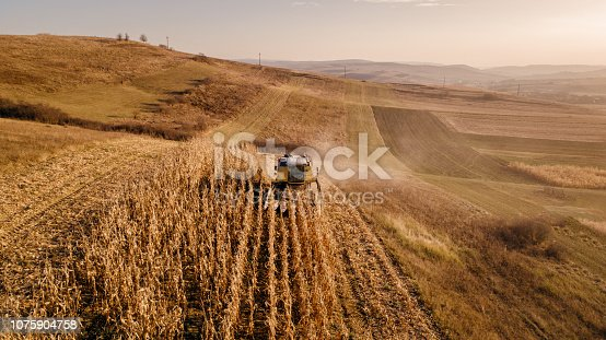 1072634078 istock photo Aerial view of combine harvesting at sunset 1075904758