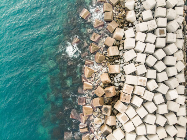 Aerial view of concrete cubes creating breakwater Aerial view of concrete cubes creating breakwater groyne stock pictures, royalty-free photos & images