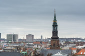 Aerial view of Copenhagen City from the The Round Tower (Rundetaarn) in rainy misty day with cloudy sky and building of St. Peter's Church bell tower