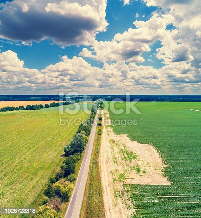 1155573645istockphoto Aerial view of countryside,  straight country road and arable fields 1028723318