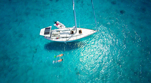 aerial view of couple snorkeling next to a luxury sailboat aerial view of honeymoon couple holding hands and snorkeling next to a luxury sailboat moored in the Caribbean snorkel stock pictures, royalty-free photos & images