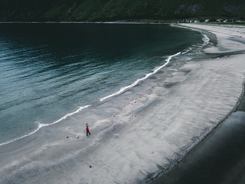 Aerial view of couple with dog staying at beautiful turquoise arctic beach in Northern Norway