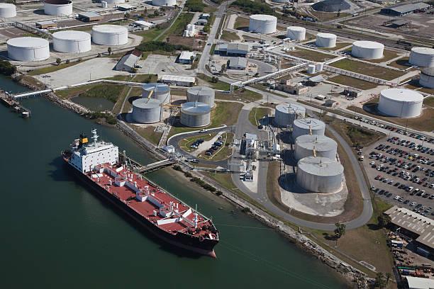 aerial view of crude oil tanker and storage tanks - brandstoftank stockfoto's en -beelden