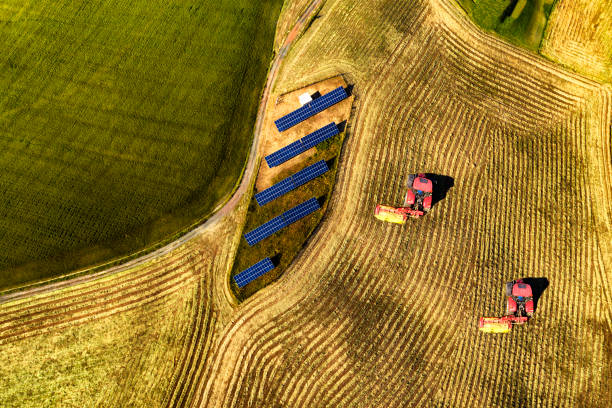 Aerial view of cultivated field with solar panel and tractors stock photo