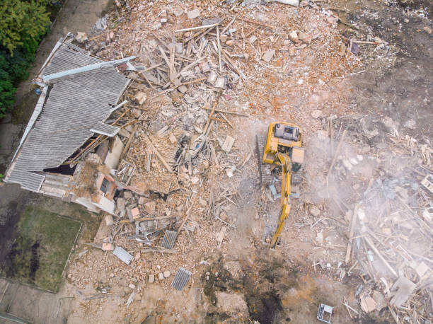 aerial view of demolition site with ruined old building and yellow excavator stock photo