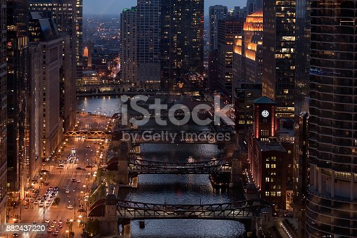 Aerial view of downtown Chicago at night with the river, bridges and city traffic.