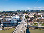 An aerial view of downtown Napa, California on a sunny day. The bridge over Napa River and the Riverfront promenade are in the foreground.