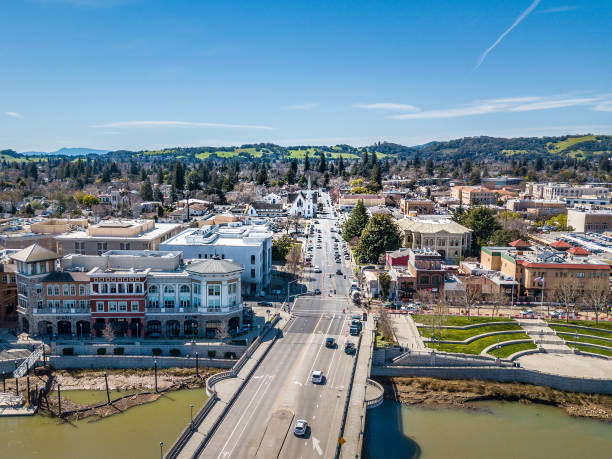 Aerial View of Downtown Napa and Riverfront An aerial view of downtown Napa, California on a sunny day. The bridge over Napa River and the Riverfront promenade are in the foreground. riverbank stock pictures, royalty-free photos & images