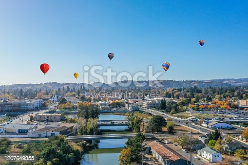 An aerial view of downtown Napa with colorful hot air balloons drifting over the city against a blue sky. Downtown River with bridges. Colorful autumn colors fill the town.