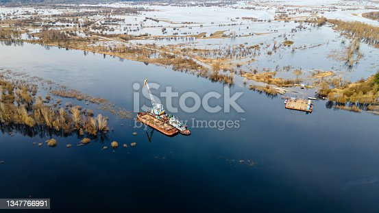 istock Aerial view of dredge replenish sand in river. Canal is being dredged by excavator. Top view of dredging boat crane. 1347766991