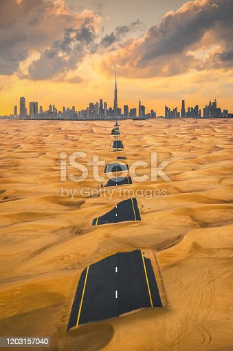 Aerial view of Dubai Downtown skyline with half desert sand road, United Arab Emirates or UAE. Financial district and business area in smart urban city. Skyscraper and high-rise buildings at sunset.