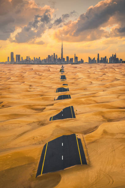 Aerial view of Dubai Downtown skyline with half desert sand road, United Arab Emirates or UAE. Financial district and business area in smart urban city. Skyscraper and high-rise buildings at sunset. stock photo