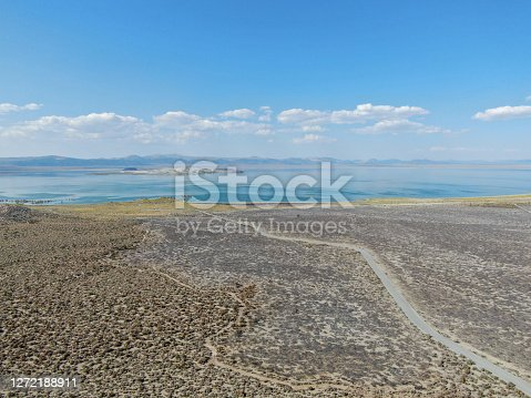 Aerial view of dusty dry desert land with Mono Lake on the background, Mono County, California, USA
