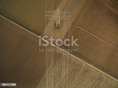 aerial view of electricity tower on agricultural fields, europe