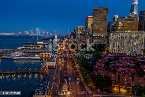 An aerial view of the Ferry Building, Financial District and the Embarcadero at blue hour. City lights twinkle and the illuminated Bay Bridge is seen in the distance.
