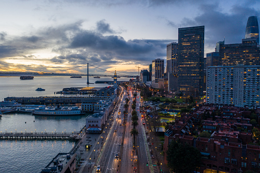 Aerial view looking down the Embarcadero in San Francisco as the sun is coming up. Ferry Building tower and early morning vehicles illuminate the road.