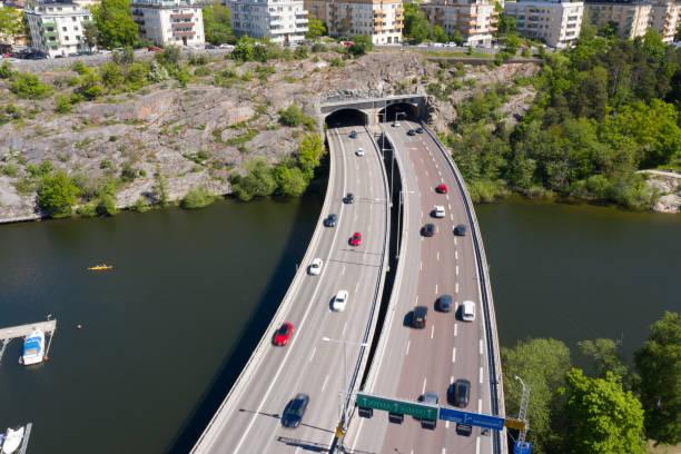 flygfoto över motorvägen essingeleden (bro) som går in i tunneln - tunnel trafik sverige bildbanksfoton och bilder