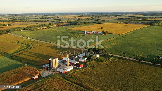 istock Aerial view of farm, red barns, corn field in September. Harvest season. Rural landscape, american countryside. Sunny morning 1270628909