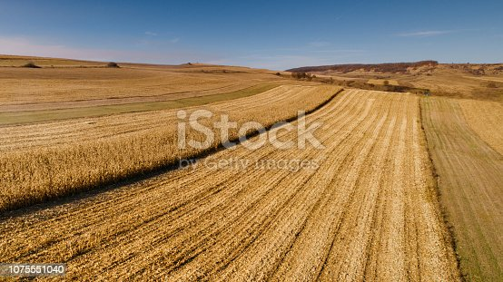 1072634078 istock photo Aerial view of farmer harvesting using tractor 1075551040
