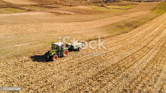 1072634078 istock photo Aerial view of farmer harvesting using tractor 1075551066