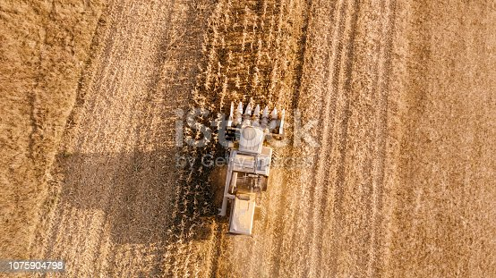 1072634078 istock photo Aerial view of farmer using combine to harvest crops 1075904798