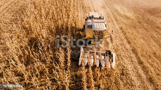 1072634078 istock photo Aerial view of farmer using tractor, harvesting combine and tools to harvest 1075904754
