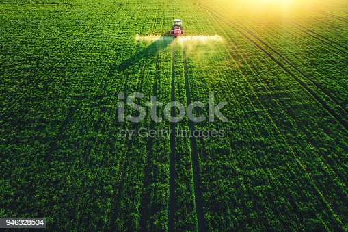 Aerial drone view of farming tractor plowing and spraying on green field.
