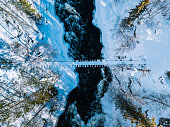 istock Aerial view of fast river with suspension foot bridge. Snow winter forest in Finland 1202226310