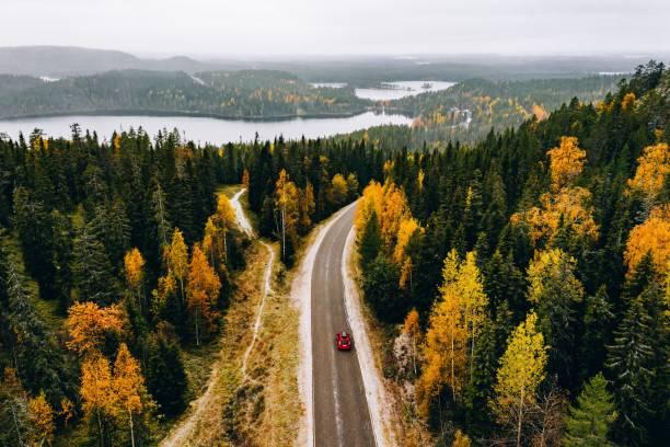 Luftaufnahme des ersten verschneiten Herbstfarbwaldes in den Bergen und einer Straße mit Auto in Finnland Lappland. – Foto