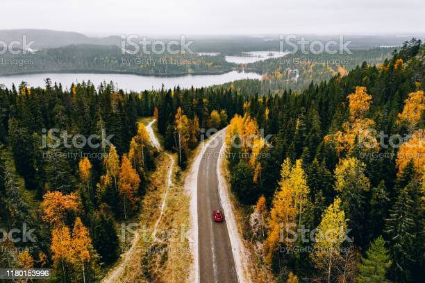 Photo of Aerial view of first snowy autumn color forest in the mountains and a road with car in Finland Lapland.