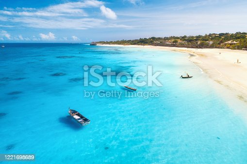 1136453253 istock photo Aerial view of fishing boats and yachts on tropical sea coast with sandy beach at sunset in summer. Indian Ocean in Zanzibar. Top view of boat, palm trees, sky, clear blue water. View from above 1221698689