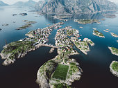 Drone photo of beautiful village of Henningsvaer, blue sea, mountains and stadium in Northern Norway