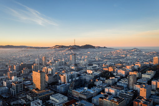 Aerial view of golden sunrise with fog over the city San Francisco looking at Sutro Tower.