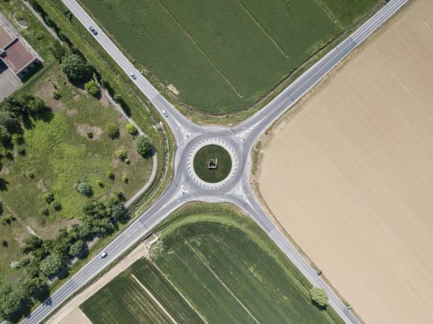 vue aérienne des quatre routes avec rond-point entouré de champs d'agro, italie - rond point photos et images de collection