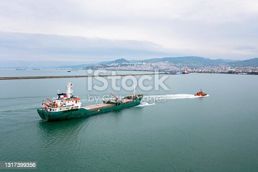 Aerial view of freight ship approaching to the port.