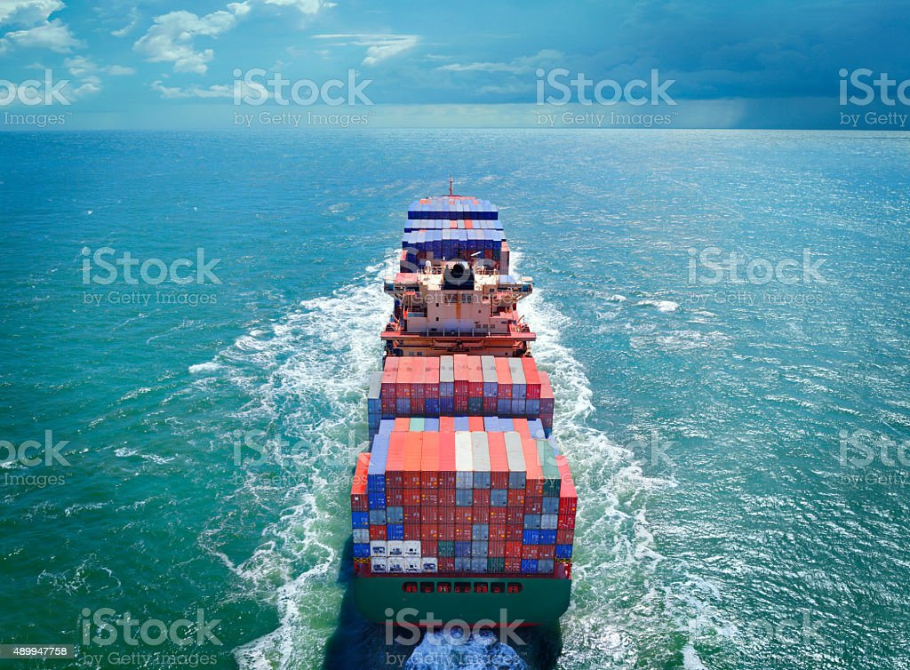 Aerial view of freight ship with cargo containers on the sea. See...