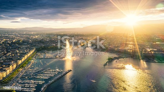 high angle view of Geneva city panoramic from drone point at sunset with famous travel destination jet d'eau and Geneva Lake.