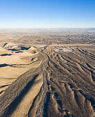 An aerial view shows eroded gullies leading towards the city of Las Vegas, Nevada. This beautiful desert area is full of tributary canyons with colorful, unique and dramatic geology.