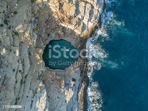 Giola is natural rock pool in Thasos island from Greece. People jumping to sea, fresh water fill this natural pool vie waves. This place is famous touristic place in Thasos.