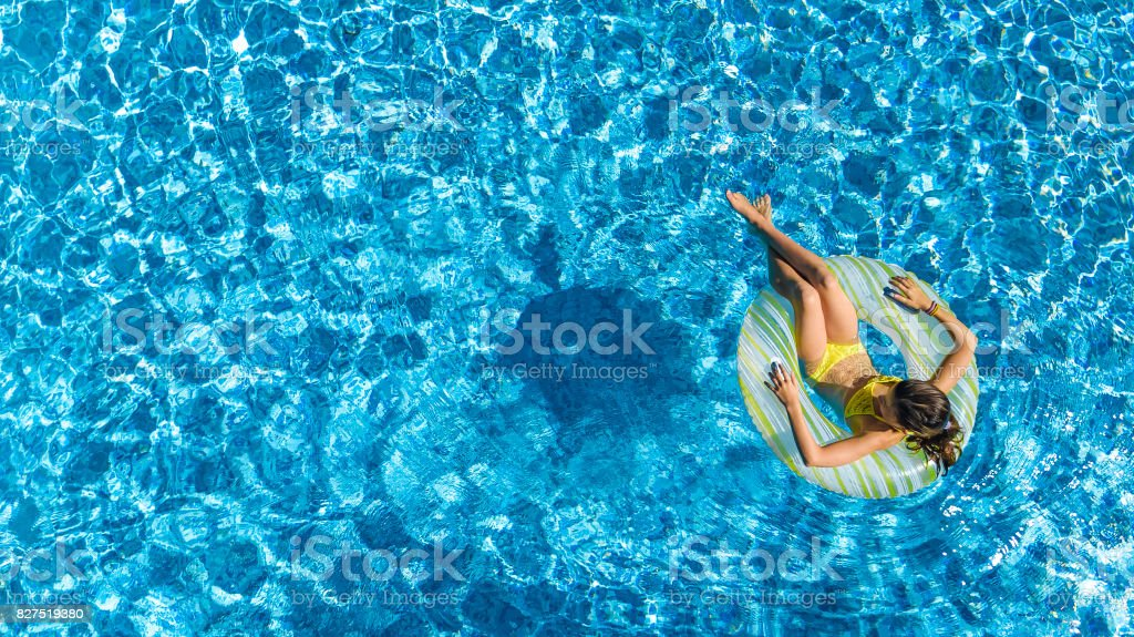 Aerial view of girl in swimming pool from above, kid swim on inflatable ring donut and has fun in water on family vacation stock photo
