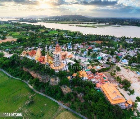 Aerial view (drone shot) of golden church with big buddha statue and rice field in Wat Tham Sua, Kanchanaburi, Thailand