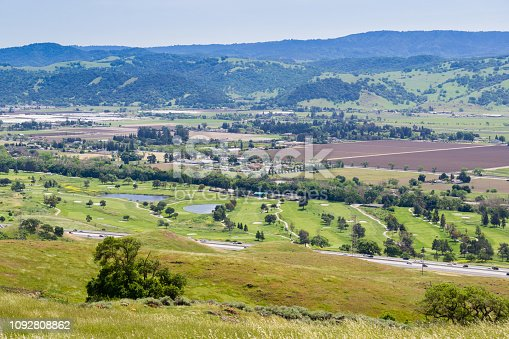 Aerial view of golf course and agricultural fields, mountain background, south San Francisco bay, San Jose, California
