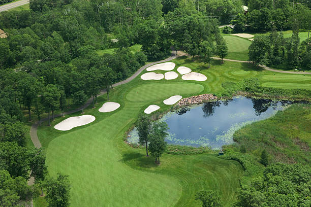 Aerial view of golf green with traps, pond and trees stock photo