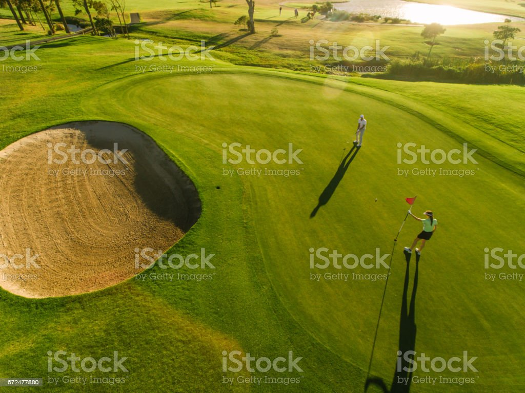 Aerial view of golfers on putting green stock photo
