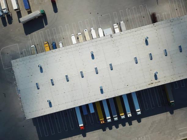 aerial view of goods warehouse. logistics center in industrial city zone from above. aerial view of trucks loading at logistic center - magazyn budynek przemysłowy zdjęcia i obrazy z banku zdjęć