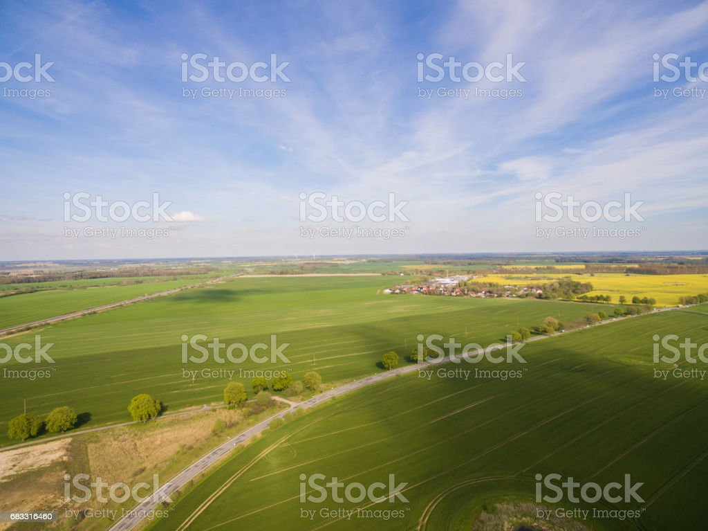 Aerial view of green agricultural fields with a country road and a smal city in the under blue sky in germany zbiór zdjęć royalty-free