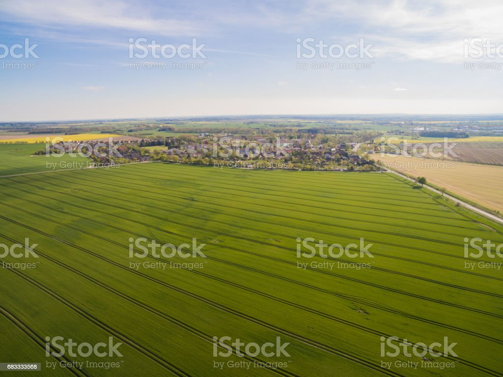 Aerial view of green agricultural fields with a country road and a smal city in the under blue sky in germany royalty-free stock photo