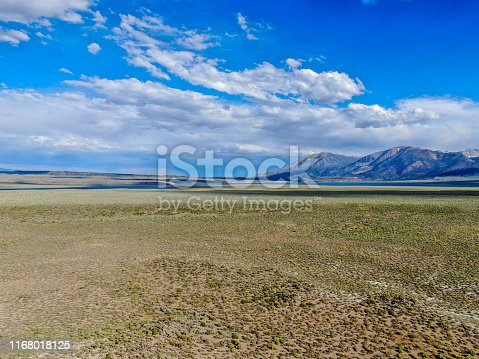 istock Aerial view of green arid wetland with mountain range on the background during clouded summer 1168018125